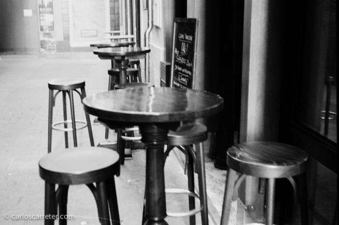 Mesas y banquetas en los bares del Tubo de Zaragoza. Fotografía tomada con una Zeiss Ikon Contessa 35 sobre negativo en blanco y negro cromogénico.