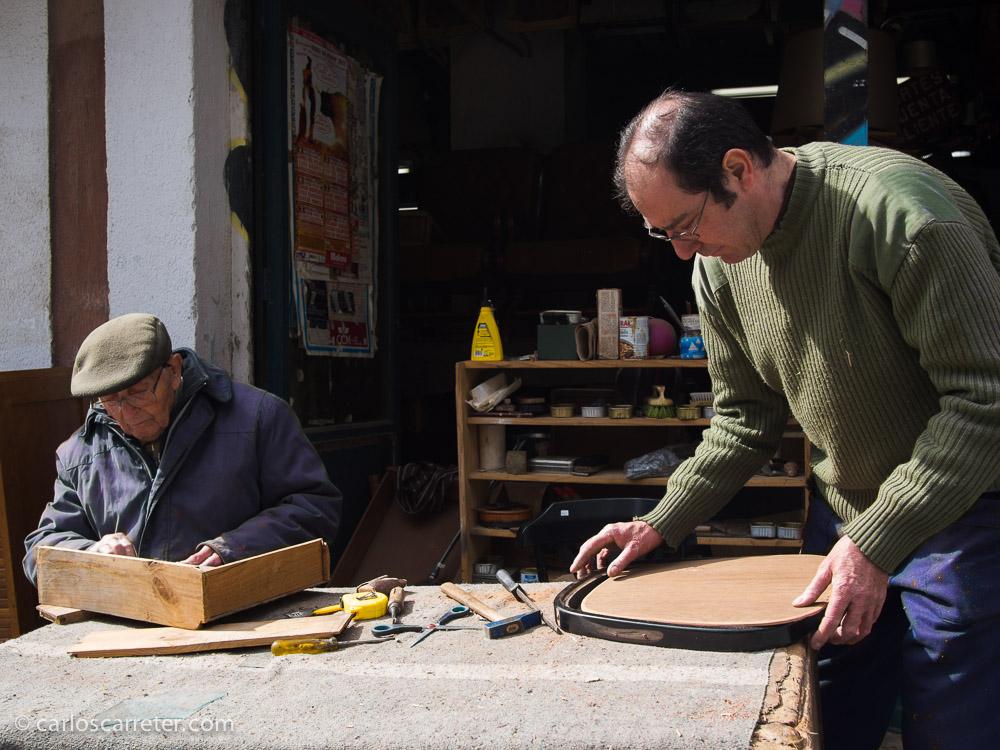 Algunos anticuarios trabajan al aire libre restaurando sus piezas, aprovechando la luz natural y la bondad del tiempo atmosférico.