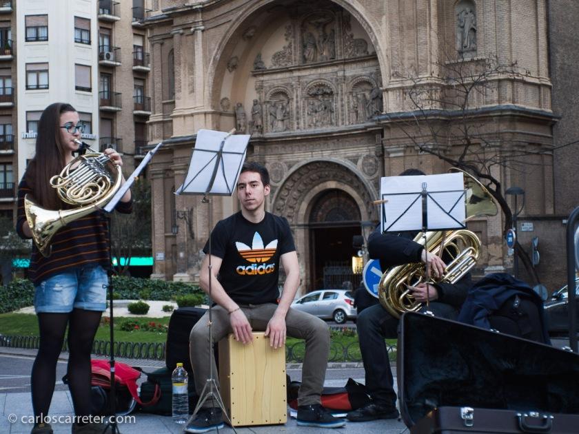 """La música tiene gran importancia en la historia entre los dos protagonistas. Y últimamente por Zaragoza, encontramos muchos grupitos de jóvenes músicos, estudiantes de conservatorio, convertidos en músicos callejeros, porque las cosas deben andar realmente mal. Como este grupo de metales en Santa Engracia. Por cierto que la música era una de las """"artes liberales"""". Curiosamente, encuadrada en el """"quadrivium"""", junto con la aritmética, la geometría y la astronomía. No con el """"trivium"""" que era más de letras como los protagonistas de esta historia. Qué cosas."""