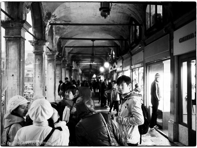 Turistas asiáticos en los soportales de la Piazza San Marco.