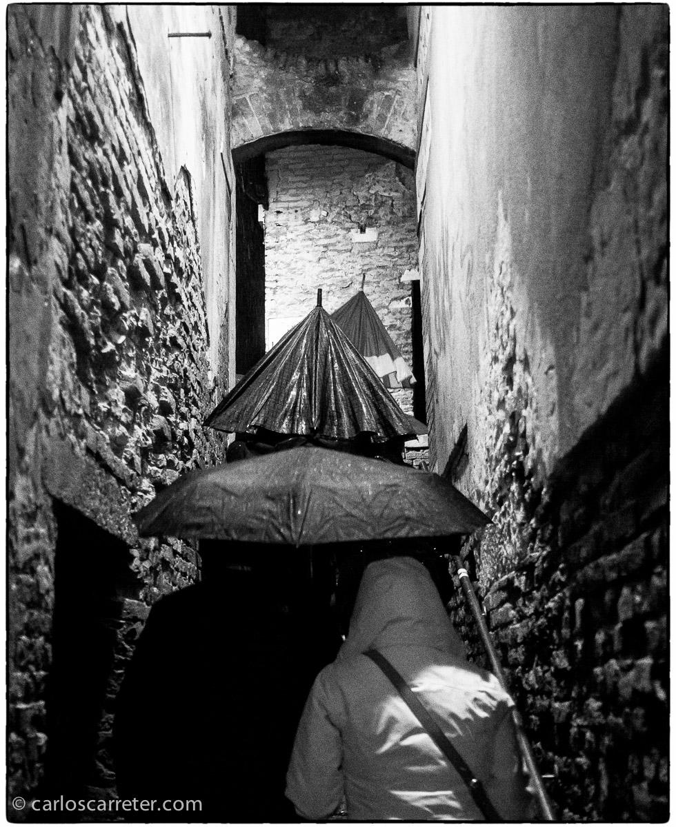 La dificultad para avanzar con el paraguas en alguno de los estrechos callejones que forman el dédalo de vías públicas de la ciudad de los canales.