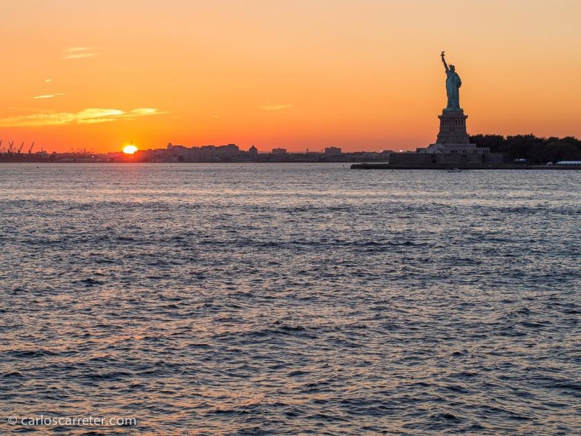 Puesta de sol desde el ferry de Staten Island, con la silueta característica de la estatua de la Libertad.