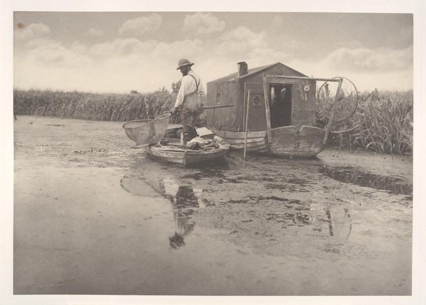 """Se trata de una fotografía de Penter Henry Emerson, tomada entre 1885 y 1886, presumiblemente en el dominio público por su antigüedad, titulada """" An Eel-Catcher's Home"""" (El hogar de un pescador de anguilas), donada al museo en 2008 por Joyce F. Menschel."""