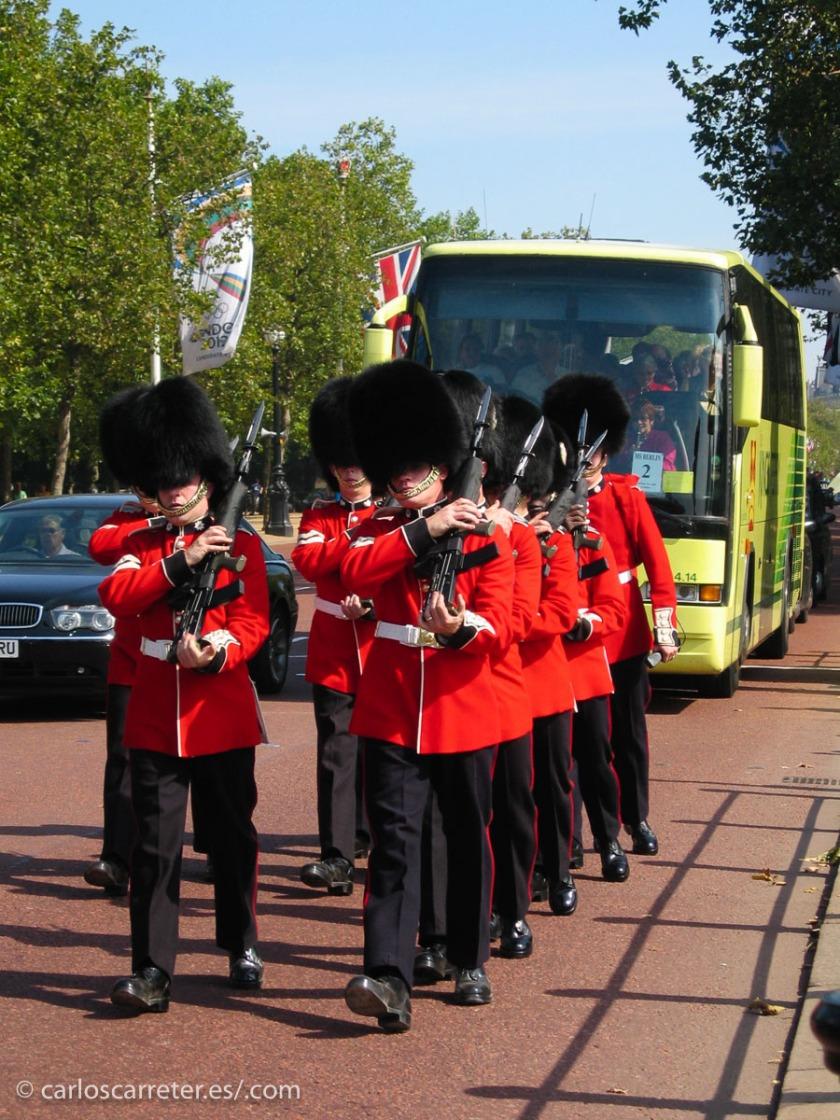 Uno soldados de la guardia de Buckingham Palace atascan el tráfico el Mall londinense.